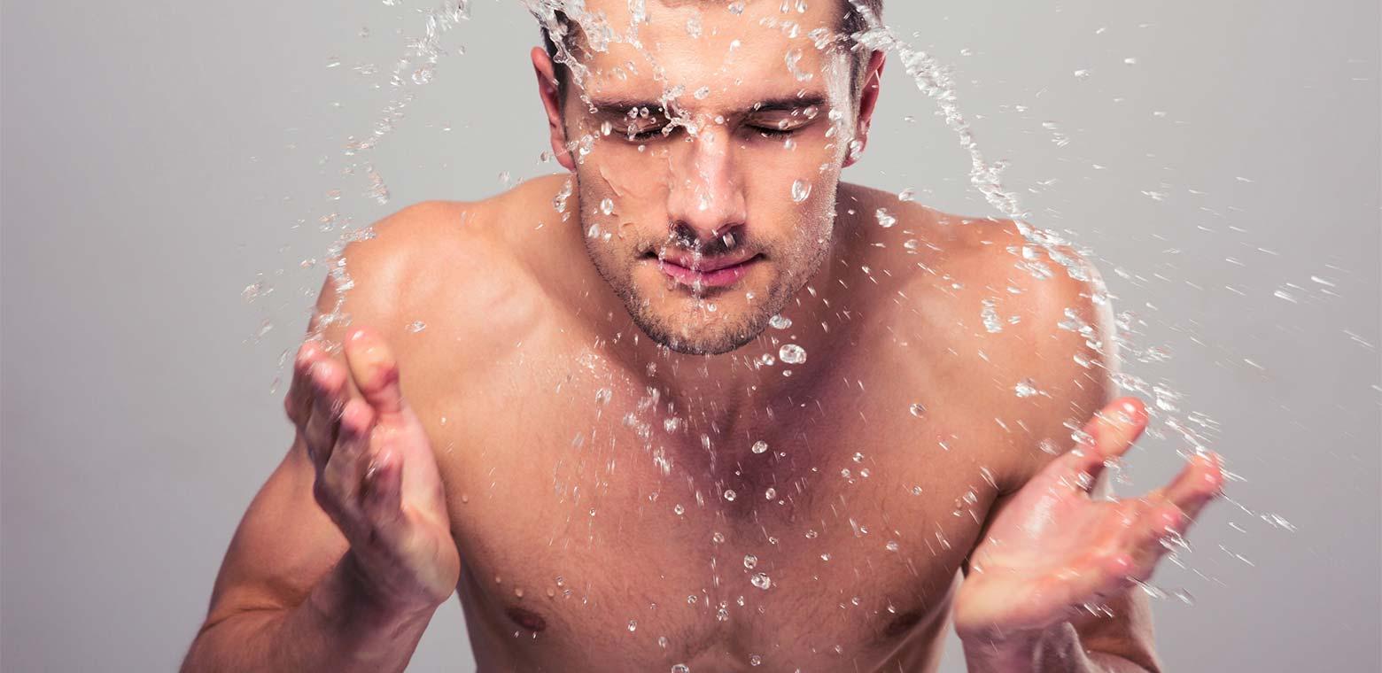 man splashing water on his face